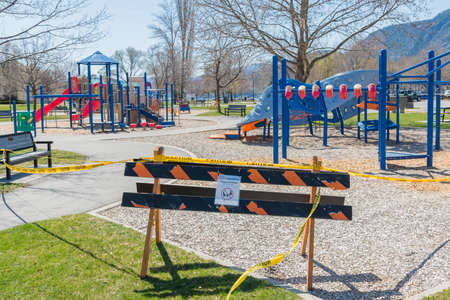 Penticton, British Columbia/Canada - April 16, 2020: cordon tape and signs block  the children's playground at Skaha Park during the coronavirus pandemic 版權商用圖片 - 145015350