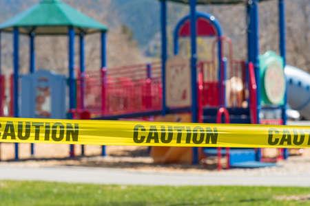 Close-up of cordon tape blocking off a children's playground during coronavirus pandemic
