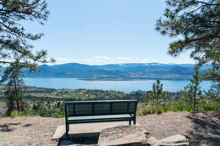 Park bench at scenic viewpoint on Kettle Valley Rail Trail with view of Okanagan Lake and Naramata
