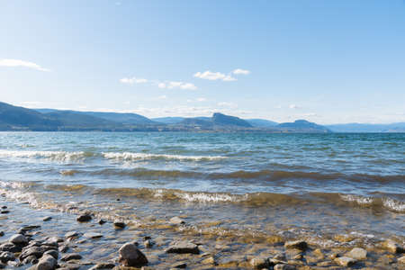 Sunny afternoon view of Okanagan Lake with clear blue sky and mountains in background 版權商用圖片