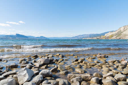 View of waves rolling onto rocky beach on Okanagan Lake with view of blue sky and mountains
