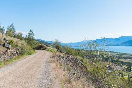 View of Kettle Valley Rail Trail high above village of Naramata and Okanagan Lake