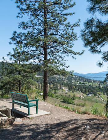Scenic viewpoint on Kettle Valley Rail Trail with park bench overlooking Okanagan Valley and Okanagan Lake 版權商用圖片