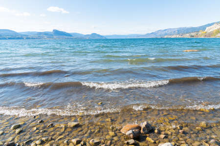 Close-up view of scenic Okanagan Lake reflecting blue sky and sunshine, with view of beach and mountains