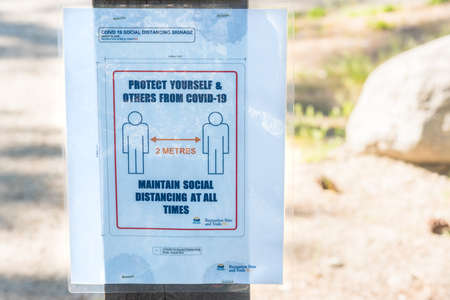 May 5, 2020 - Naramata, BC, Canada: sign posted  on the Kettle Valley Rail Trail during the coronavirus pandemic, reminding trail users to practice social distancing for their protection. 新聞圖片