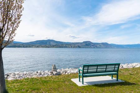 Park bench with view of Okanagan Lake at Naramata Wharf Park, BC, Canada