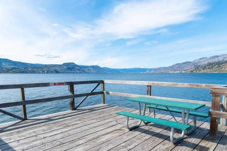 Picnic table on Naramata Wharf with scenic view of Okanagan Lake, mountains, and blue sky