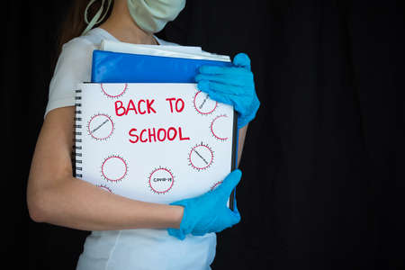 Student wearing face mask and surgical gloves and holding school books with Back To School written on notepad 版權商用圖片