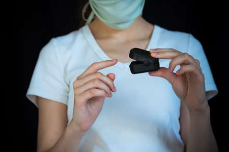 Close-up of woman wearing face mask and putting pulse oximeter on finger, with black background