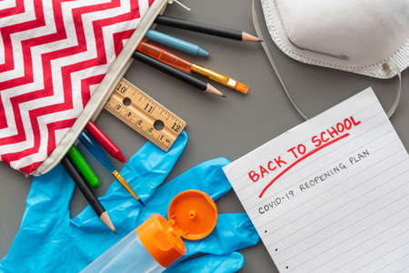 Back to school COVID-19 reopening plan, flat lay arrangement of school supplies and personal protective equipment 版權商用圖片
