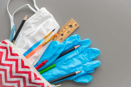 Child's pencil case with school supplies, face mask, and surgical gloves on solid gray background