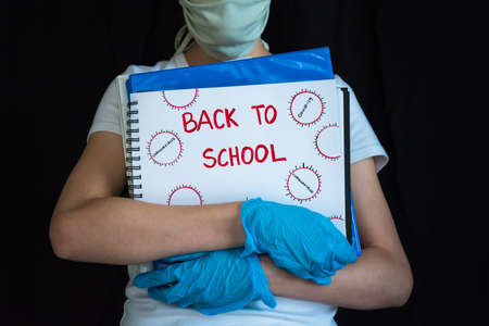 Student wearing face mask and gloves, holding school books. Concept of reopening schools during COVID-19 pandemic.