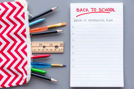 Back to school COVID-19 school reopening plan concept shot. Flay lay arrangement with school supplies