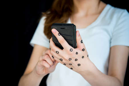 Concept photo of woman holding cell phone with coronavirus on hand