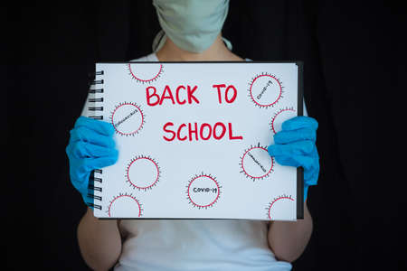 Teenage girl wearing face mask and surgical gloves, holding up notebook that says Back to School