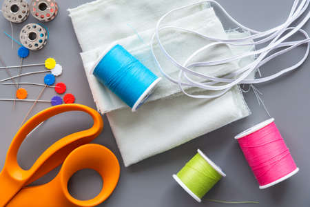 Arrangement on grey background of sewing equipment need to make a fabric face mask
