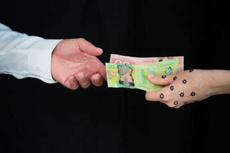 Woman with COVID-19 on hand giving Canadian dollars to man 版權商用圖片