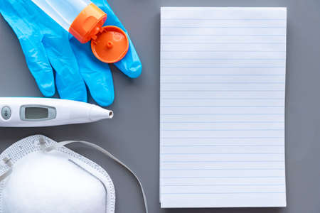 Lined note pad paper, medical N95 mask, digital thermometer, surgical glove, and hand sanitizer on gray background with copy space
