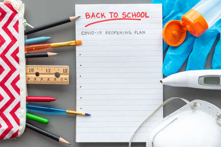 Back to school flat lay on gray background with school supplies and medical equipment.