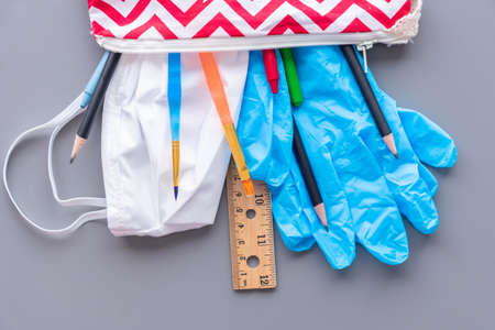 Back to school during coronavirus COVID-19 pandemic. Child's pencil case filled with school supplies, gloves, and face mask.