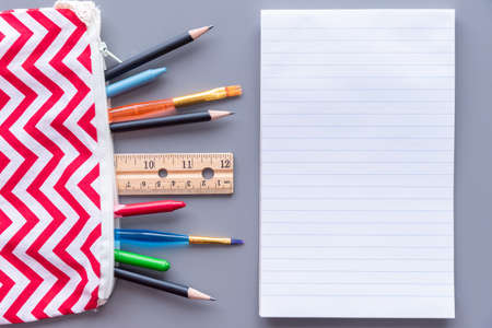 Lined paper on table beside pencil case full of stationery supplies
