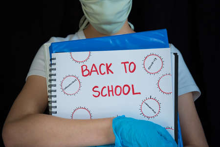 Close-up of student wearing face mask and surgical gloves, holding school books with Back to School written on cover 版權商用圖片