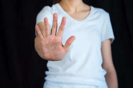 Caucasian woman in white shirt with black background, holding out hand in stop gesture