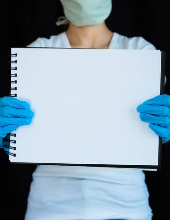 Close-up of blank notebook page held up by woman wearing face mask and surgical gloves with black background 版權商用圖片