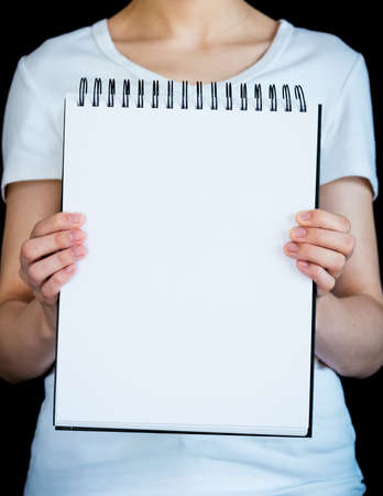 Close-up of blank page of note pad held up by woman wearing white t-shirt against black background 版權商用圖片