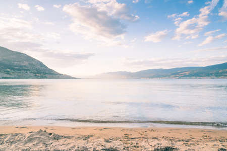 View of sun setting over Okanagan Lake with colours reflecting in water