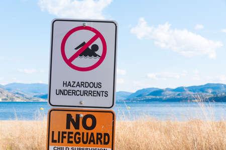 Hazardous undercurrents warning sign on beach at lake