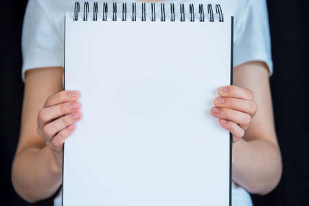 Close-up of woman's hands holding out a spiral bound notebook with a blank page for copy space