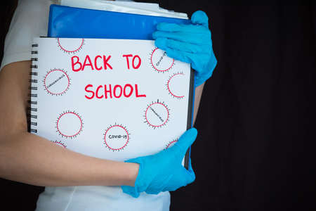 Back to school concept image during COVID-19 pandemic. Student wearing gloves and holding school books