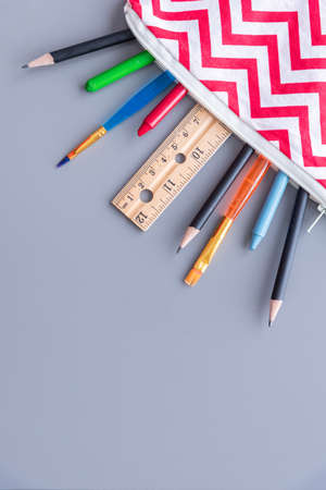 Child's pencil case with school supplies flat-lay arrangement on solid gray background
