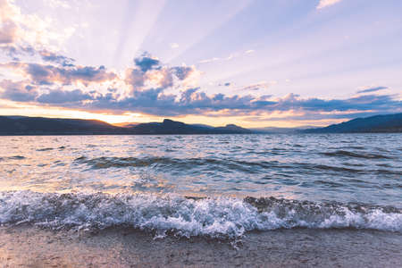 Okanagan Lake waves crashing onto Three Mile Beach at sunset with view of Okanagan Valley mountains 版權商用圖片