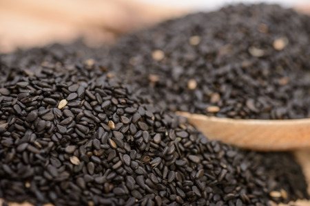 black sesame seeds on the wooden board Stock Photo