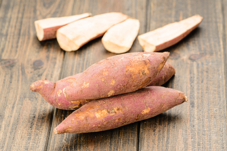 red sweet potatoes on the wooden board.