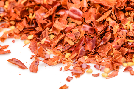 crushed red peppers: red chilli flakes on the white background Stock Photo