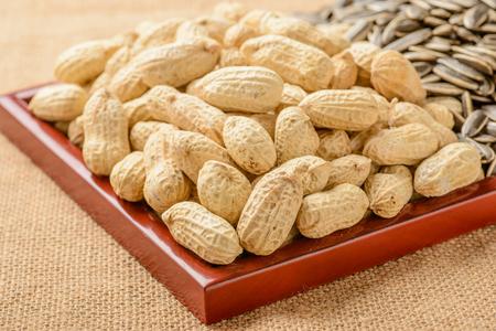 semillas de girasol: cacahuetes y semillas de girasol en la placa de madera Foto de archivo