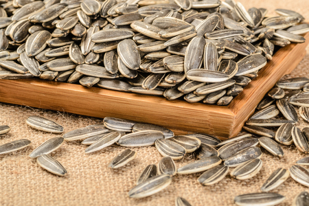 baked sunflower seeds in the wooden plate photo