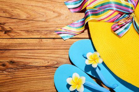 flipflops: beach hat and flip-flops on the wooden board