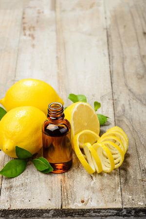 lemon essential oil and fresh lemon peel on the wooden board Archivio Fotografico