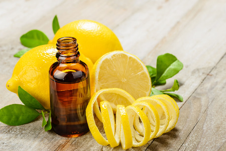 lemon essential oil and lemon fruit on the wooden board Standard-Bild
