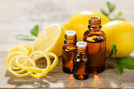 lemon essential oil and lemon fruit on the wooden board 스톡 콘텐츠
