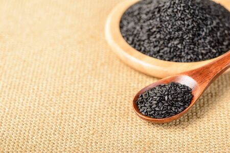 ajonjoli: sésamo negro en la cuchara de madera