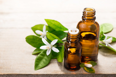 neroli essential oil in the brown glass bottle, with fresh white neroli flower and green leaves. Archivio Fotografico