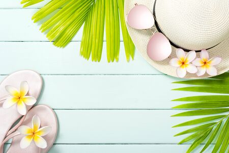 palm leaves and beach accessories on the wooden board Stock Photo