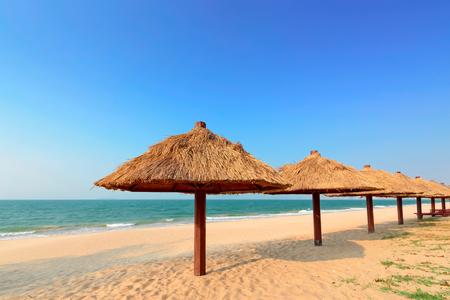 golden straw umbrella on the summer beach
