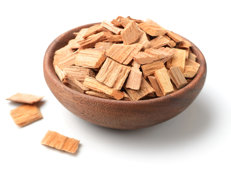 pieces of sandalwood in the wooden bowl, isolated on white