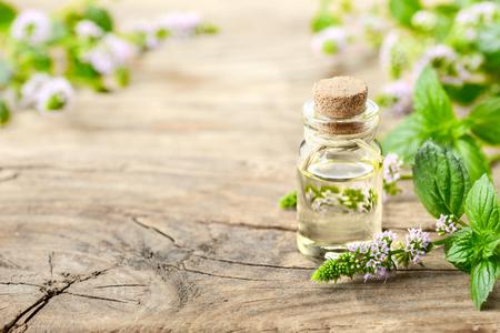 Pepermuntetherische olie en pepermuntbloemen op de houten lijst